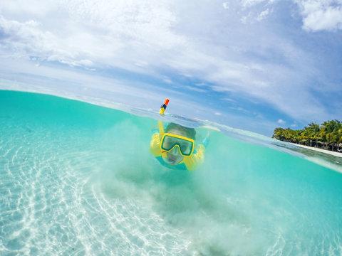 Split underwater photo of child in mask snorkeling in blue ocean water near tropical island