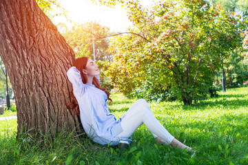 Tuinposter Ontspanning Young woman sitting under tree in summer park