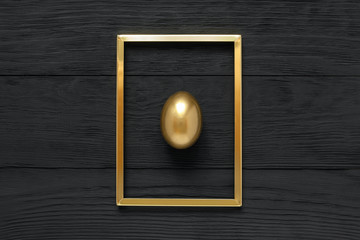 Golden egg in frame on black wooden background. Making money, savings, pensions and successful investment concept, top view