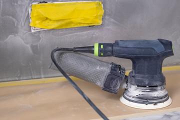 Random-orbit disc sander, refinishing piece of custom sand stucco Wall mural