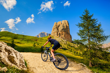 Woman cycling in Cortina d'Ampezzo, stunning Cinque Torri and Tofana in background. Woman riding MTB trail. South Tyrol province of Italy, Dolomites.