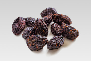 Prunes, or plums in dried form on a light gray background
