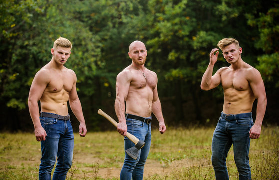 Taking break. brutal guys pose with naked torso. handsome guys with sexy body. Sports and leisure. mesomorph. three muscular men with axe. athletic man use ax. bodybuilders in jeans. Three sexy guys