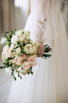 The bride holds a beautiful wedding bouquet with white and pink roses. Vertical photo