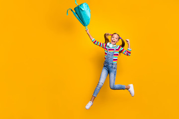 Yeah i pass exams. Ful size photo crazy energetic ecstatic schoolkid jump throw blue bag rucksack wear striped sweater denim casual style jeans isolated bright shine yellow color background