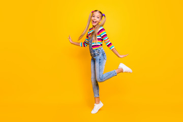 Full length photo of dream dreamy candid funny kid enjoy autumn fall weekends holiday feel rejoice wear colorful sweater footwear isolated over yellow color background Wall mural