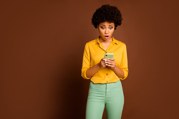 Photo of shocked dark skin curly lady holding telephone hands influencer open mouth read negative...