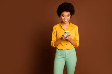 Photo of amazing dark skin wavy lady holding telephone hands influencer writing new blog post creative youth theme wear yellow shirt green trousers isolated brown color background