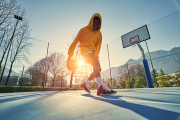 Athletic black man showing his backetball skills on court outdoors. Fotomurales