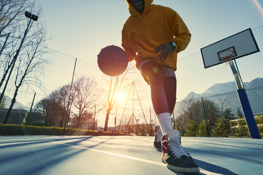 Athletic black man showing his backetball skills on court outdoors.