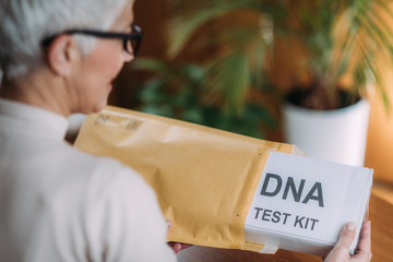 Senior Woman Doing a Mailed DNA Test at Home