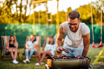 Young positive man grilling meat on a barbecue outdoors, for friends.