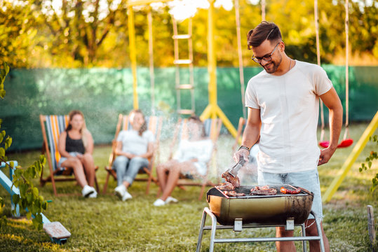 Summertime fun. Portrait of a young man grilling meat on the barbecue grill outdoors.