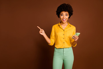 Shocked crazy afro american girl student use smartphone point finger copyspace indicate social media sale scream wow wear yellow green trendy pants trousers isolated brown color background
