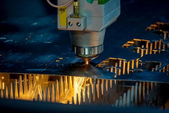 The close up scene of fiber laser cutting machine cutting the sheet metal  plate. The hi-technology sheet metal manufacturing process by laser cutting machine.