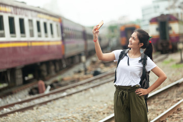 asian girl are taking pictures at the train station before traveling by train, destination nature trip in summer