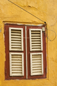 An old wooden window with closed shutters in a yellow ochre painted brick wall in Willemstad, Curacao.