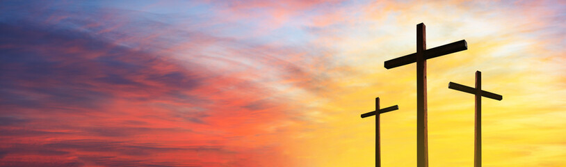 Cross of Jesus Christ empty over dramatic sunrise sky panorama with sclouds.  Easter concept