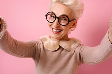Cheerful grandma taking selfie on the phone. Photo of kind elderly woman wears eyeglasses on pink background.