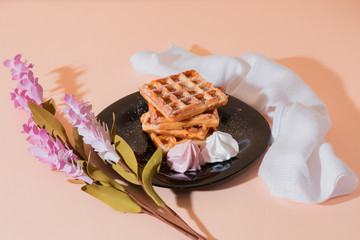 Sweet delicious dessert, homemade baked goods for breakfast. Belgian European soft waffles on a black plate and meringue