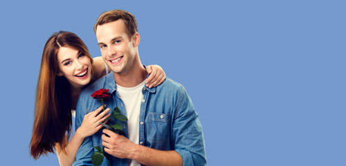 Love, relationship, dating, flirting, romantic concept - portrait picture of happy couple with flower, looking at camera. Blue color background. Copy space for some text.