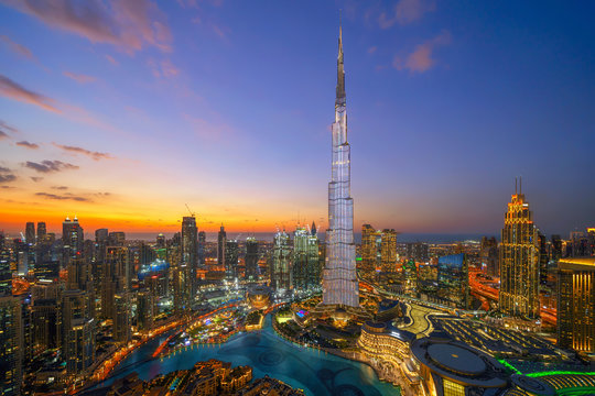 Aerial view of Burj Khalifa in Dubai Downtown skyline and fountain, United Arab Emirates or UAE. Financial district and business area in smart urban city. Skyscraper and high-rise buildings at night.