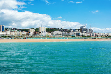 View of Brighton town seafront, houses and beach from the pier in East Sussex, UK