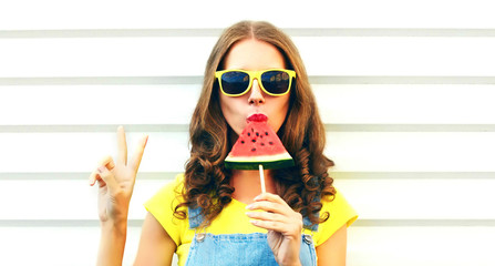 Portrait young woman eating ice cream shaped watermelon over white background