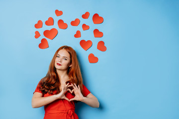 caucasian redhaired lady radiating love isolated over blue background. woman glows with happiness, small hearts above her head. celebration, st valentines day, 14 february, love, peop e concept Fotobehang