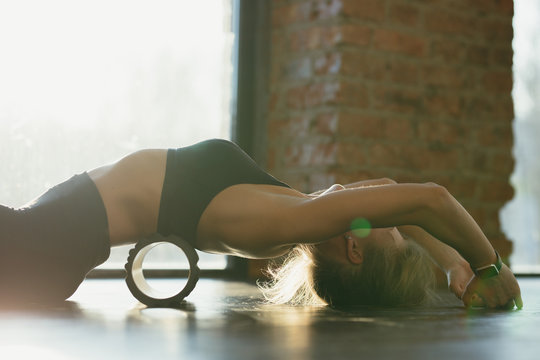Fitness trainer girl in black leggings and a T-shirt in the training room flexes with a massage roll on the floor in the loft room
