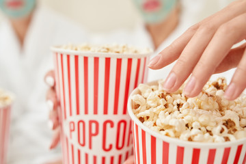 Selective focus of popcorn boxes in female arms.