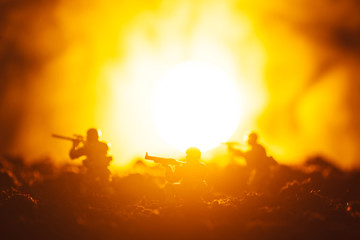 Battle scene with toy warriors in smoke and sunset at background
