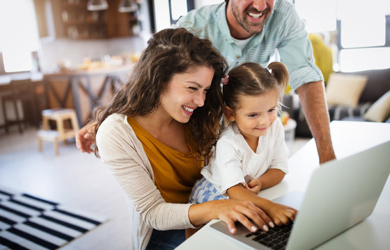 Happy family spending time at home and using laptop
