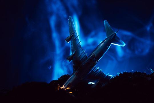 Battle scene with crash of toy plane with blue smoke on black background
