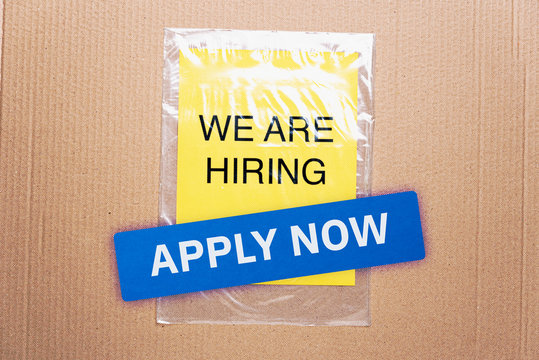 Apply now job button here hiring resources register online concept. We are hiring printed on yellow paper on transparent plastic bag with cardboard background.