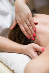 Woman getting a stress relieving pressure point massage on her neck by a health therapist