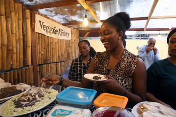 A lady serves herself a plate of vegan food at a gathering for vegans in a restaurant in Lagos