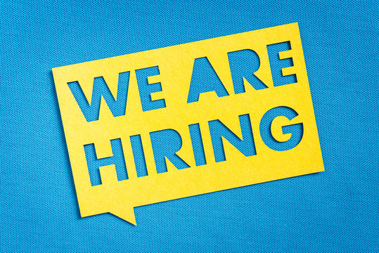 """""""WE ARE HIRING"""". Yellow speech bubble banner on blank blue textured background. Job vacant and employment concept with copy space."""