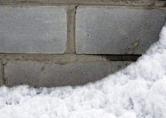 Backgrounds and textures. On the gray brick wall is white fluffy snow.