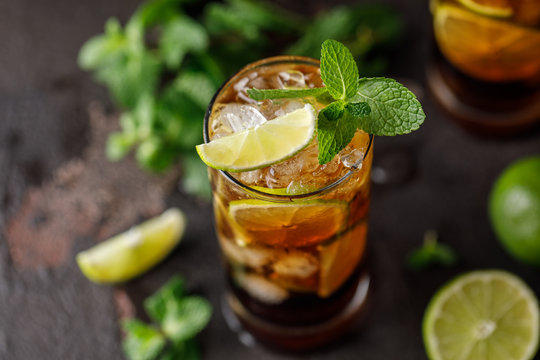 Cuba Libre with brown rum, cola, mint and lime. Cuba Libre or long island iced tea cocktail with strong drinks