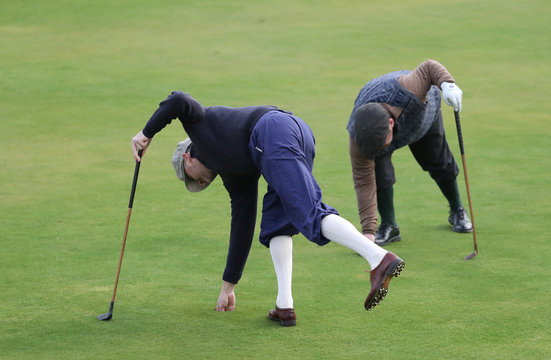 A competitor retrieves his ball from the hole during the Scottish Hickory Golf Tour at Braid Hills Edinburgh, Scotland