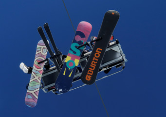 Snowboarders and a skier sit in a chairlift at Schlick 2000 ski resort near Neustift