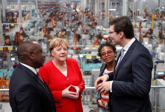 South Africa's President Cyril Ramaphosa, German Chancellor Angela Merkel and South Africa's Minister of Small Business Development Khumbudzo Ntshavheni, listen to Milan Nedeljkovic, Head of Production at the BMW SA Group Plant in Rosslyn, Pretoria
