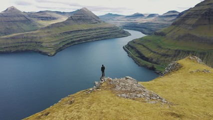 Wall Mural - Flying around a hiker at the top of a mountain above Funningur on Faroe Islands