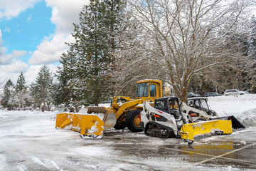 Snow removal vehicles sit idle in a parking lot of a suburban American City after a winter storm.