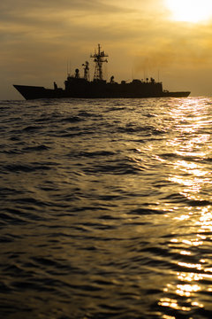 A military nato us navy boat frigate sailing in the ocean with antennas and missiles
