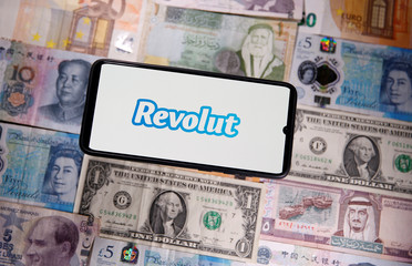 A smartphone displays a Revolut logo on top of banknotes is in this illustration