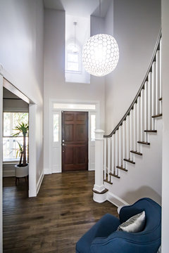 Interior Front Entrance Lobby of home with Vaulted cathedral ceilings and a window with a dark stained wood front door and globe shaped chandelier hanging light