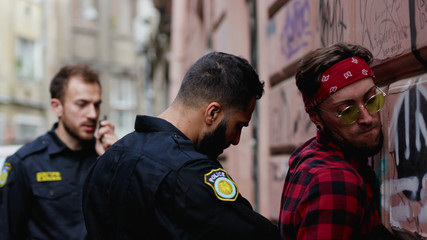 Police arrest. View of young man drug dealer near the wall being handcuffed. Policeman seacrhes an offender and leads him to the car. City life.