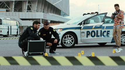 Police raid. Two police officers examine evidence in crime area. Criminological expert takes pictures on camera to provide detailed investigation.